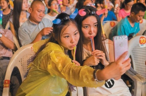 Attendees of the Qingdao International Beer Festival taking a selfie with a smartphone, Shandong province, China, August 2015