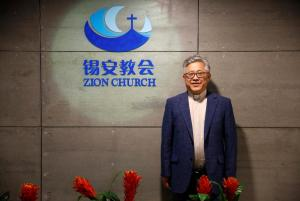"The head pastor of the Zion church in Beijing Jin Mingri poses for picures in the lobby of the unofficial Protestant ""house"" church in Beijing"