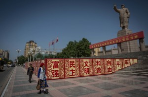A Uyghur woman walks pass a statue of Mao Zedong in the