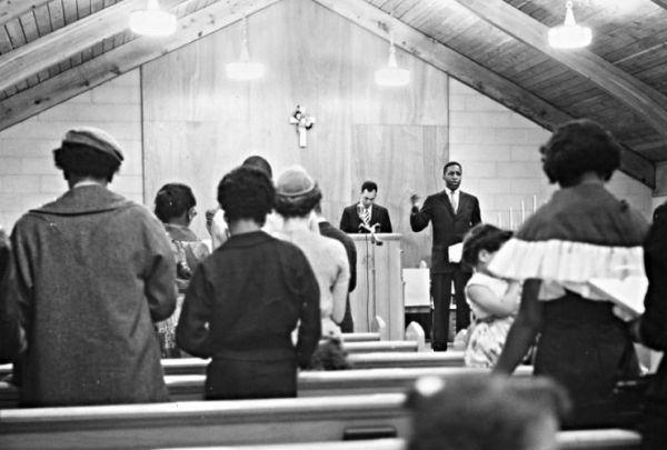 Gerald_Hughes,_Cleveland_School_Teacher,_Leads_the_Lee_Heights_Community_Church_(Cleveland,_Ohio)_Congregation_in_Song,_1960_(16458543170)
